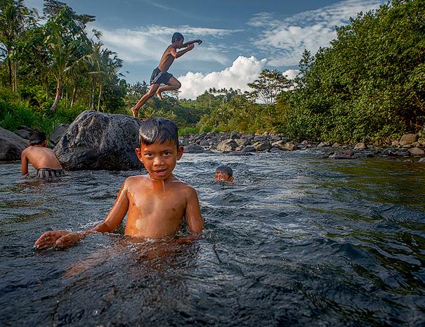 Children swimming in the river in Sidemen / Bali