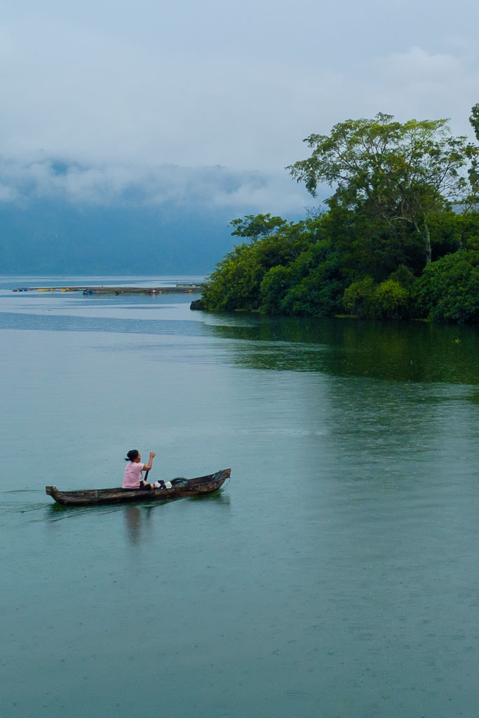 A balinese lady rowing in her boat while it is raining on the lake