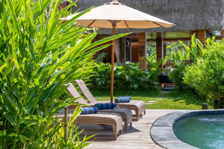 Sun beds at the infinity pool of vacation rental Villa Uma Dewi Sri in Sidemen in Bali